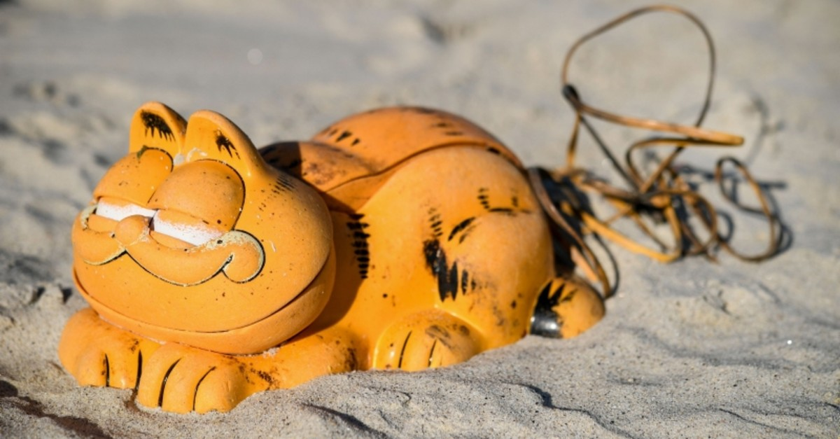 A plastic 'Garfield' phone is displayed on the beach on March 28, 2019 in Plouarzel, western France, after being collected from a sea cave by environmental activists. (AFP Photo)