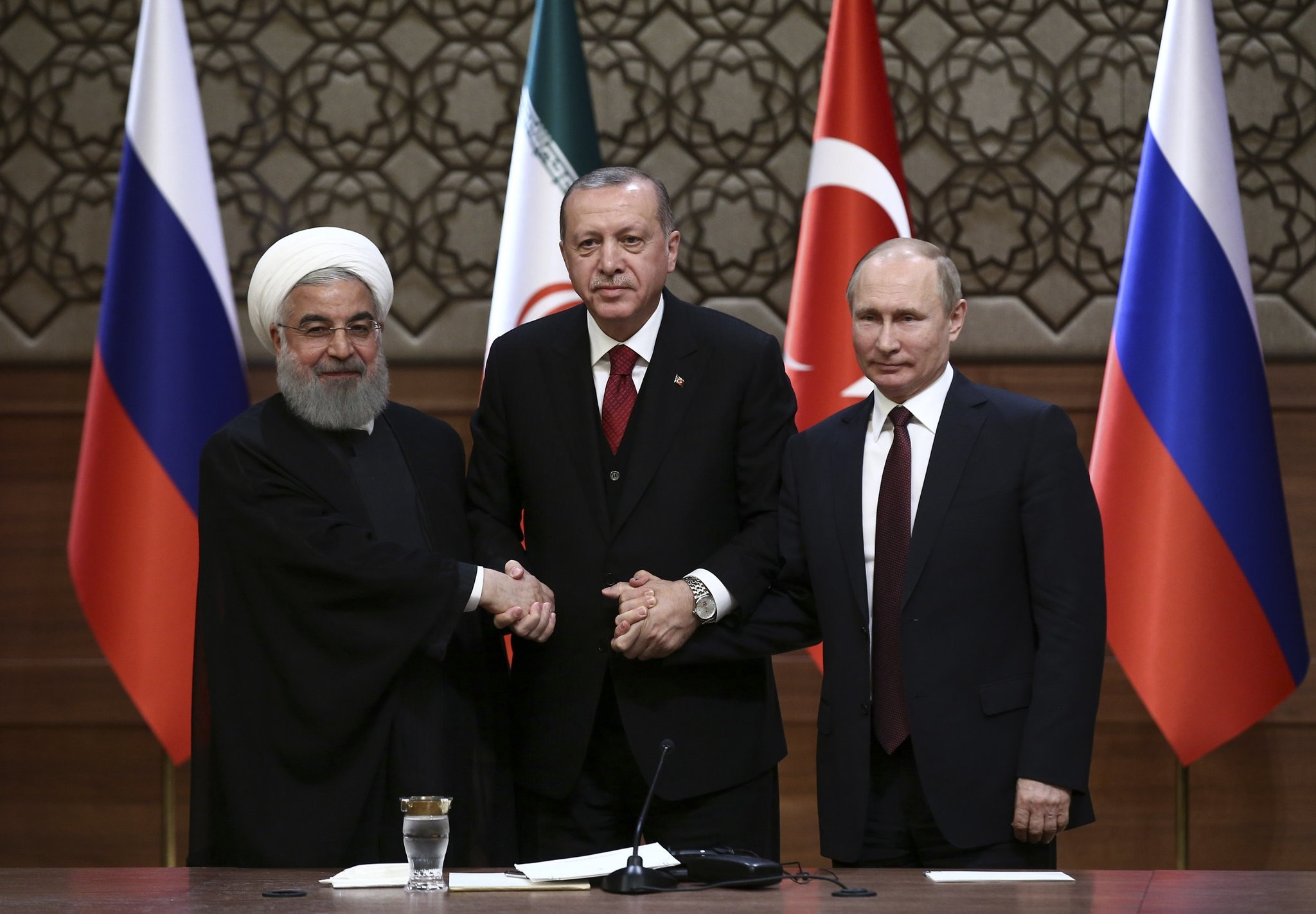 President Recep Tayyip Erdou011fan (C), Iranu2019s President Hassan Rouhani (L) and Russiau2019s President Vladimir Putin (R) shake hands after a joint conference as part of a tripartite summit on Syria in Ankara, April 4.