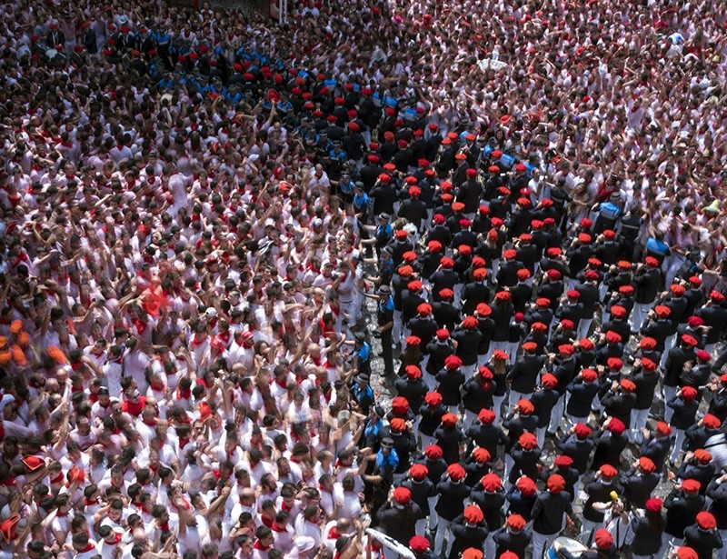 Revellers with hands up as fife and drum music begins (R) and a line of police hold back the revellers as the Festival of San Fermin begins in Pamplona, northern Spain, July 6, 2018. (EPA Photo)