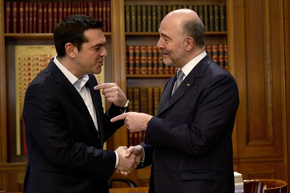 Greek Prime Minister Alexis Tsipras (L) shakes hands with top EU economic affairs official Pierre Moscovici during their meeting in Athens Thursday.