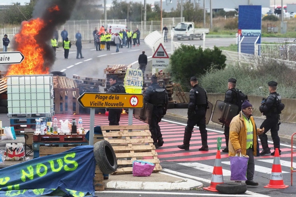 Gendarmes walk by a burning barricade as they disperse protesters blocking the fuel depot of Port-La-Nouvelle, Nov. 20.
