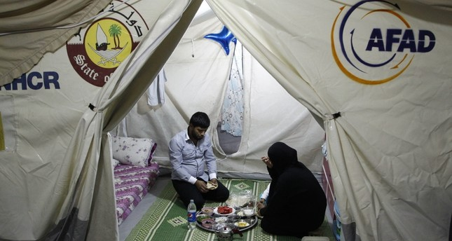 A Syrian family in a tent at the refugee camp in Kahramanmaraş have 'suhoor', a meal before the fast.