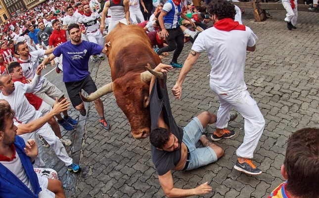 A 'mozo', is caught by the horn of a bull of Miura ranch during the last 'encierro,' or running-with-the-bulls, of the Sanfermines festivities in Pamplona, Spain, 14 July 2019. (EPA Photo)