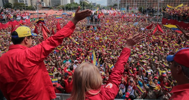 Handout picture released by the Venezuelan presidency showing Maduro (L) and his wife Cilia Flores wave at the crowd during a gathering to mark the 20th anniversary of the rise of power of the late Hugo Chavez, in Caracas on February 2, 2019 (AFP)