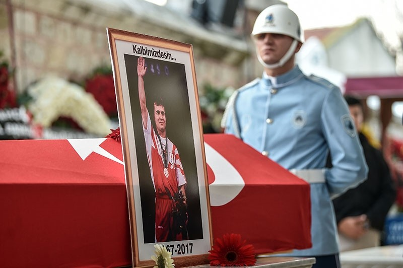 A police officer stays next to a coffin of Turkey's legendary triple Olympic gold-medal winning weightlifter Naim Su00fcleymanou011flu on Nov. 19, 2017 during his funeral cerenomy in Istanbul. (AFP Photo)