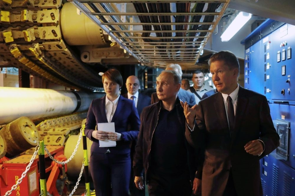 Russian President Vladimir Putin (C), accompanied by Gazprom Chief Executive Officer Alexei Miller (R), visits the Pioneering Spirit pipelaying ship in the Black Sea on June 23, 2017.