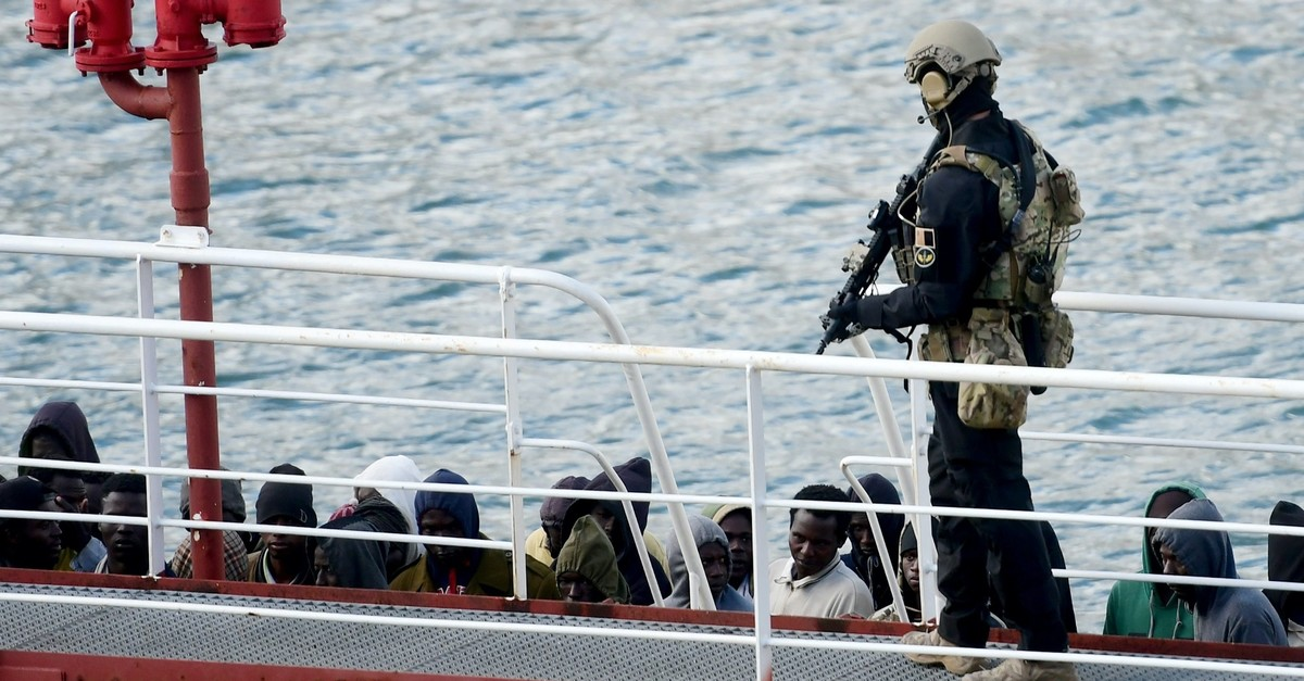 An armed policeman stands guard after migrants disembarked from the Motor Tanker El Hiblu 1, Valletta, March 28, 2019.