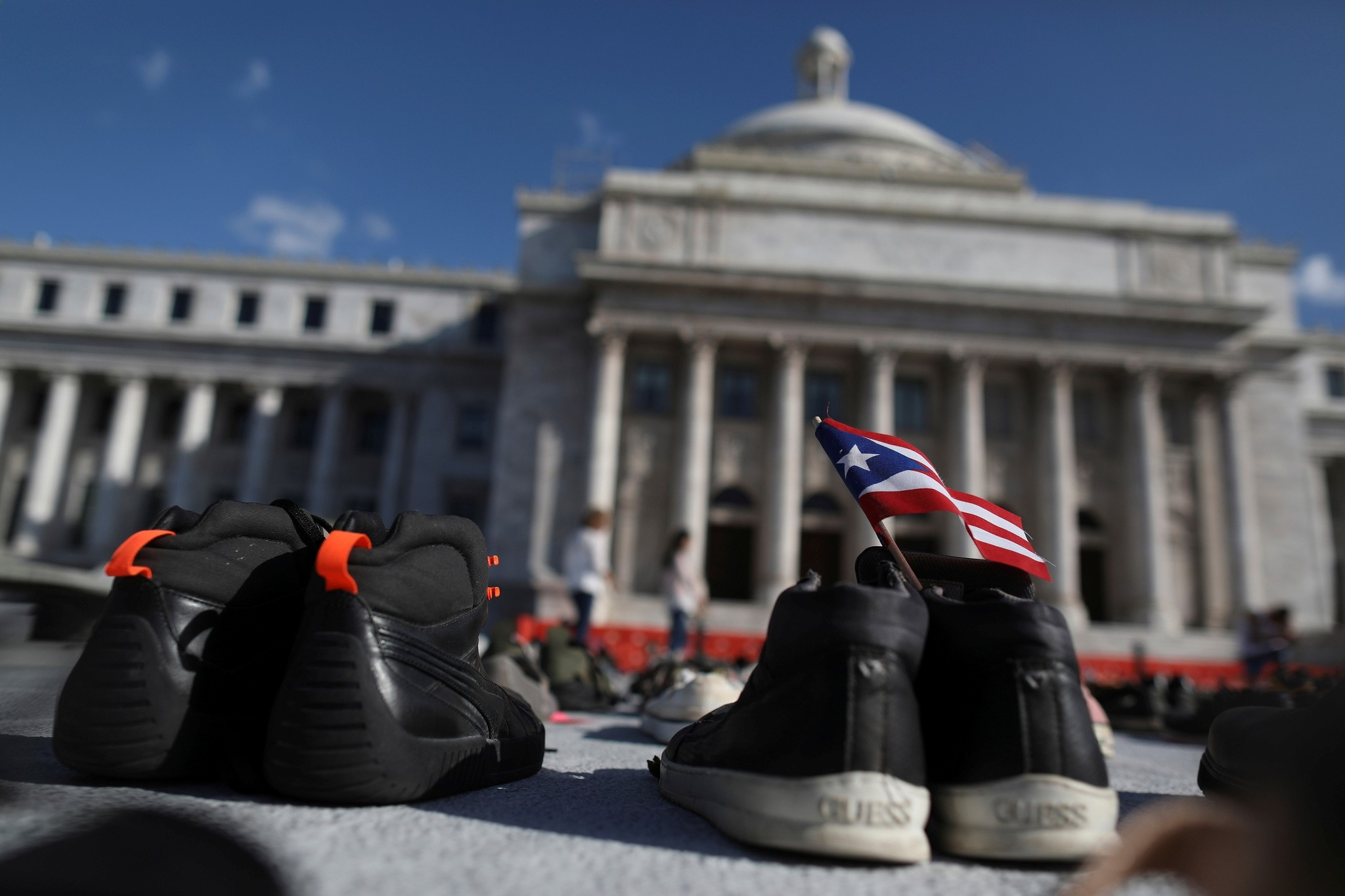 A Puerto Rican flag is seen on a pair of shoes as hundreds of pairs of shoes displayed at the Capitol to pay tribute to Hurricane Maria's victims, in San Juan, Puerto Rico June 1, 2018. (Reuters Photo)