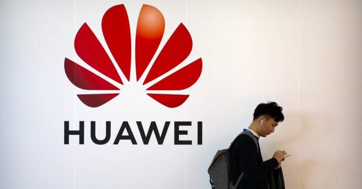 In this Oct. 31, 2019, file photo, a man uses his smartphone as he stands near a billboard for Chinese technology firm Huawei at the PT Expo in Beijing. (AP Photo)