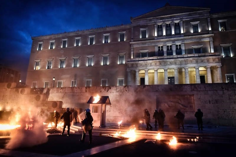 Greek riot police stand amid Molotov coctails and tear gas in front of the Greek parliament in Athens on May 18, 2017. AFP Photo