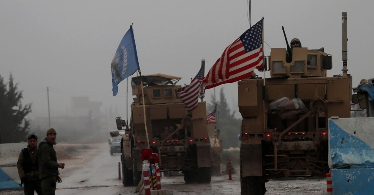 U.S. military vehicles drive through a checkpoint in Manbij as they head to their base on the outskirts of the northern Syrian province, Dec. 30, 2018.