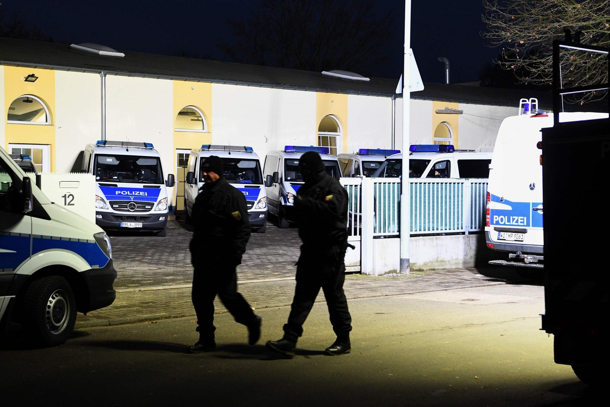 Policemen walk past their cars standing on the grounds of the Bilal mosque in the Griesheim district of Frankfurt am Main, western Germany, on February 1, 2017. (AFP Photo)