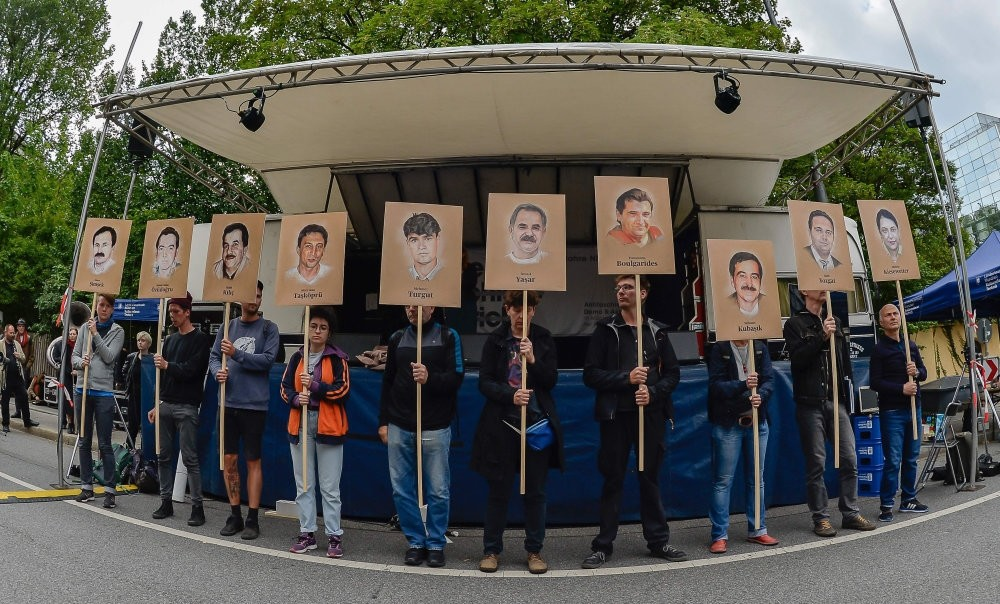 Protesters hold up signs with pictures of the victims of the Neo-Nazi cell NSU before the proclamation of a sentence in the trial against Beate Zschaepe, the only surviving member of the NSU, Munich, July 11, 2018.