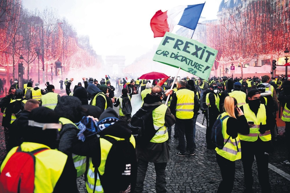 Demonstrators wearing the iconic ,yellow vests, of the French protest movement stand on the Champs u00c9lysu00e9e avenue during a rally against the government, in Paris, Dec. 8.
