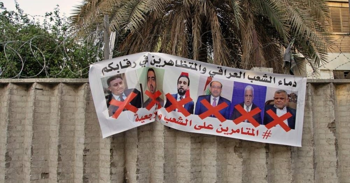 A poster with defaced pictures of Iraqi politicians and Arabic that reads, ,the blood of the protesters and the Iraqi people is on your necks, the conspirators on the people and the religious authority,, it hung on the wall near Tahrir Square, Baghdad, Dec. 26, 2019 (AP Photo)