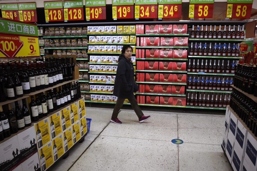 A woman walks by a section selling imported foods and beverages at Walmart in Beijing.