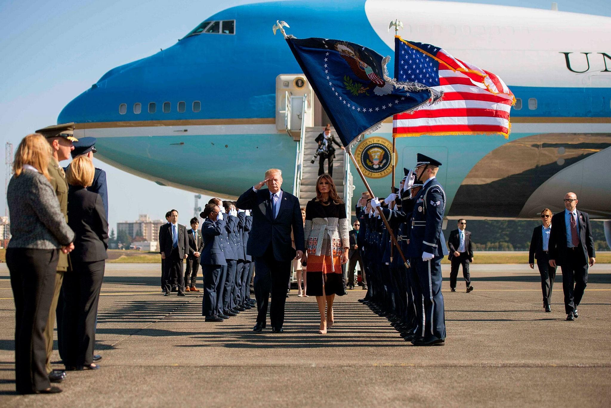 U.S. President Donald Trump and first lady Melania Trump walk through an honor cordon as they arrive at Yokota Air Base at Fussa, Tokyo, Nov. 5.
