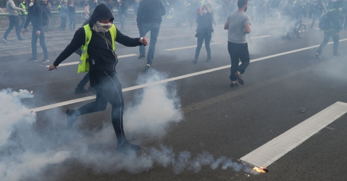 A protester prepares to kick back a tear-gas canister during a ,Yellow Vests, (Gilets Jaunes) protest in Rouen on April 6, 2019 as demonstrations are planned by the ,Yellow Vest, movement for the 21st consecutive Saturday (AFP Photo)