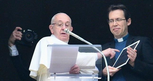 Pope Francis points to a tablet computer as he invites the faithful to download the Click to Pray, from the window of Apostolic Palace overlooking St. Peter's square in the Vatican during the weekly Angelus prayer on January 20, 2019. (AFP Photo)