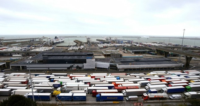 Lorries queue at the entrance to the Port of Dover ferry terminal in southern England, as bad weather causes heavy seas and delays to the cross Channel ferry, Tuesday, March 12, 2019. (PA via AP)