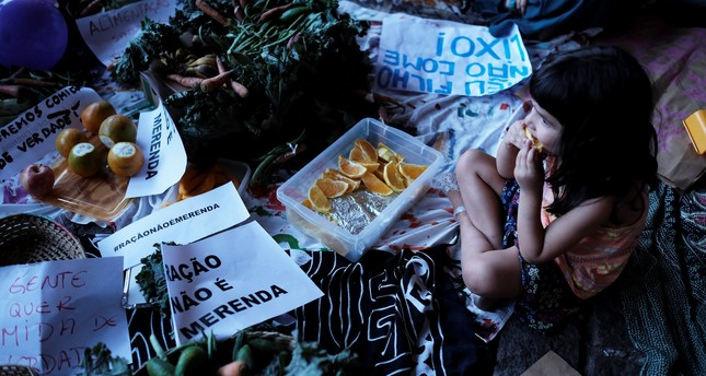 A child eats an orange next to a sign reading Food Pellets are not meals during a protest against Sao Paulo Mayor Doria's plans to serve school meals made of reprocessed food pellets in Sao Paulo, Brazil October 19, 2017. (REUTERS Photo)