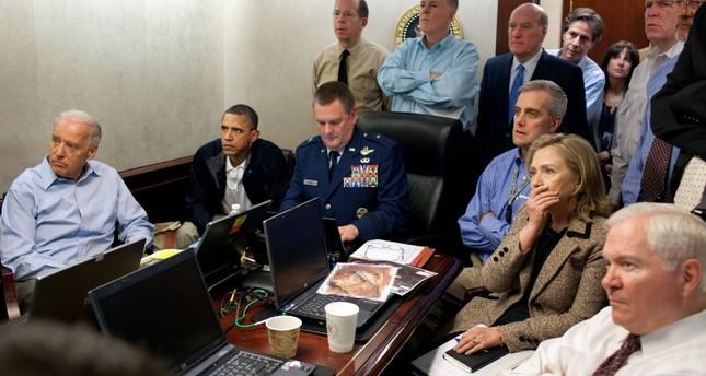 الرئيس الأمريكي باراك أوباما الثاني من اليسار ونائب الرئيس جو بايدن إلى اليسار ووزير الدفاع الأمريكي روبرت جيتس يمين ووزيرة الخارجية هيلاري كلينتون الثانية يمين مع أعضاء فريق الأمن القومي يتلقون آخر المستجدات حول مهمة قتل أسامة بن لادن في غرف