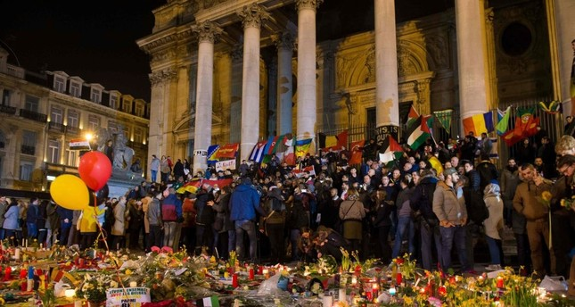 Hundreds of people gather at a makeshift memorial on March 24, 2016, two days after a triple bomb attack, claimed by the Daesh, hit Brussels' airport and the Maelbeek - Maalbeek metro station, the killing 32 people and wounding 300 others.