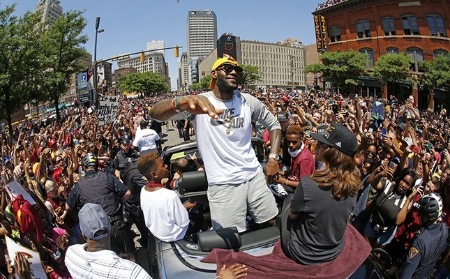 In this June 22, 2016, file photo, Cleveland Cavaliers' LeBron James, center, stands in the back of a Rolls-Royce as it makes it way through the crowd during a parade in downtown Cleveland celebrating the team's NBA championship. (AP Photo)