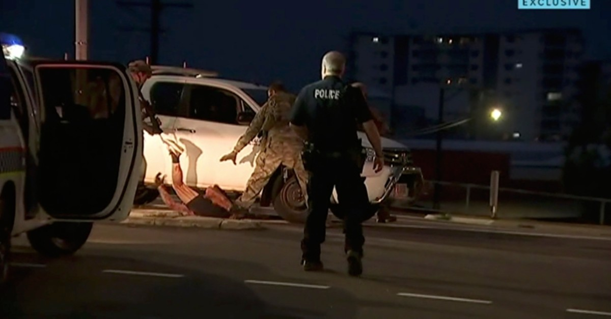 In this image made from video, police proceed to apprehend a suspect on the ground next to a white truck, Tuesday, June 4, 2019, in Darwin Australia. (AP Photo)