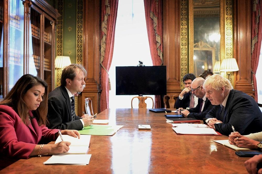Britain's Foreign Secretary Boris Johnson, right, sits opposite Richard Ratcliffe, the husband of British-Iranian Nazanin Zaghari-Ratcliffe in London. (Pool Photo via AP)