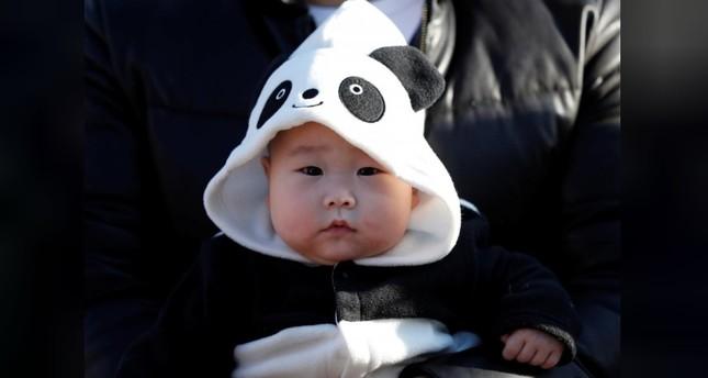 A baby wearing a costume featuring giant panda waits for starting the public debut of female baby panda Xiang Xiang, born from mother panda Shin Shin on June 12, 2017. (REUTERS Photo)