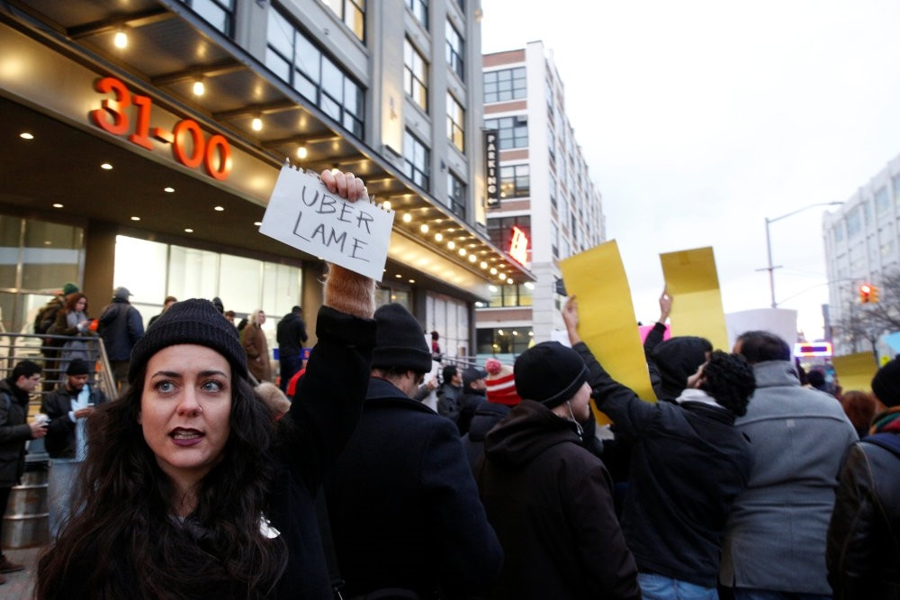 People gather to protest outside the Uber offices in Queens, New York.