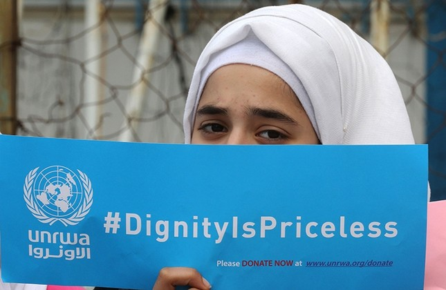 A Palestinian refugee holds a placard at a school belonging to the United Nations Relief and Works Agency for Palestinian Refugees (UNRWA) in Sebline, Lebanon, March 12, 2018. (AFP Photo)