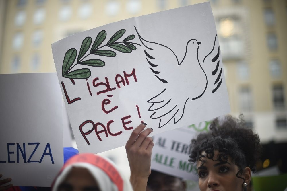 A woman holds up a poster reading ,Islam is peace, during a demonstration of Muslims speaking out against terrorism, a week after Paris terrorist attacks, Milan, Nov. 21, 2015. (AFP Photo)
