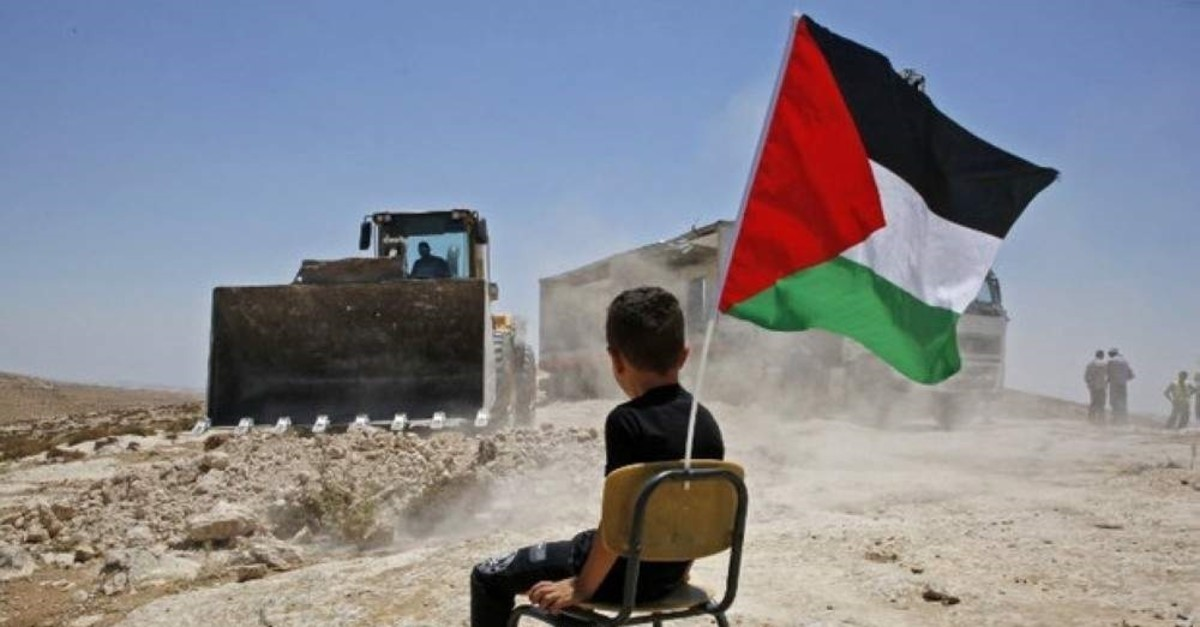 A Palestinian boy sits on a chair with a national flag as Israeli authorities demolish a school site in the village of Yatta, in the occupied West Bank, July 11, 2018. (AFP Photo)