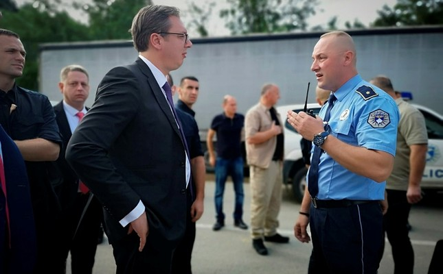 A Kosovo police officer speaks to Serbia's president Aleksandar Vucic, left, to say he cannot continue his trip to the village of Banje due to roadblocks, in Zubin Potok, Kosovo, Sunday, Sept. 9, 2018. (Serbian Presidency via AP)