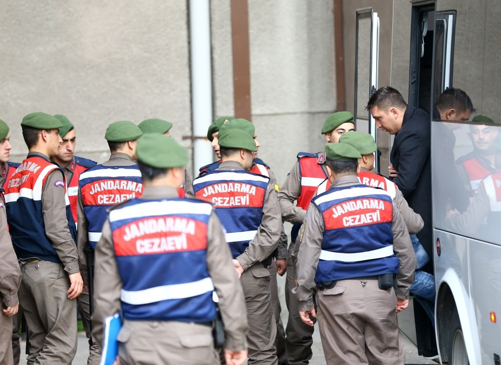 Gendarmerie officers escort a defendant stepping out of a bus into the courtroom before a trial of pro-coup troops in Ankara.