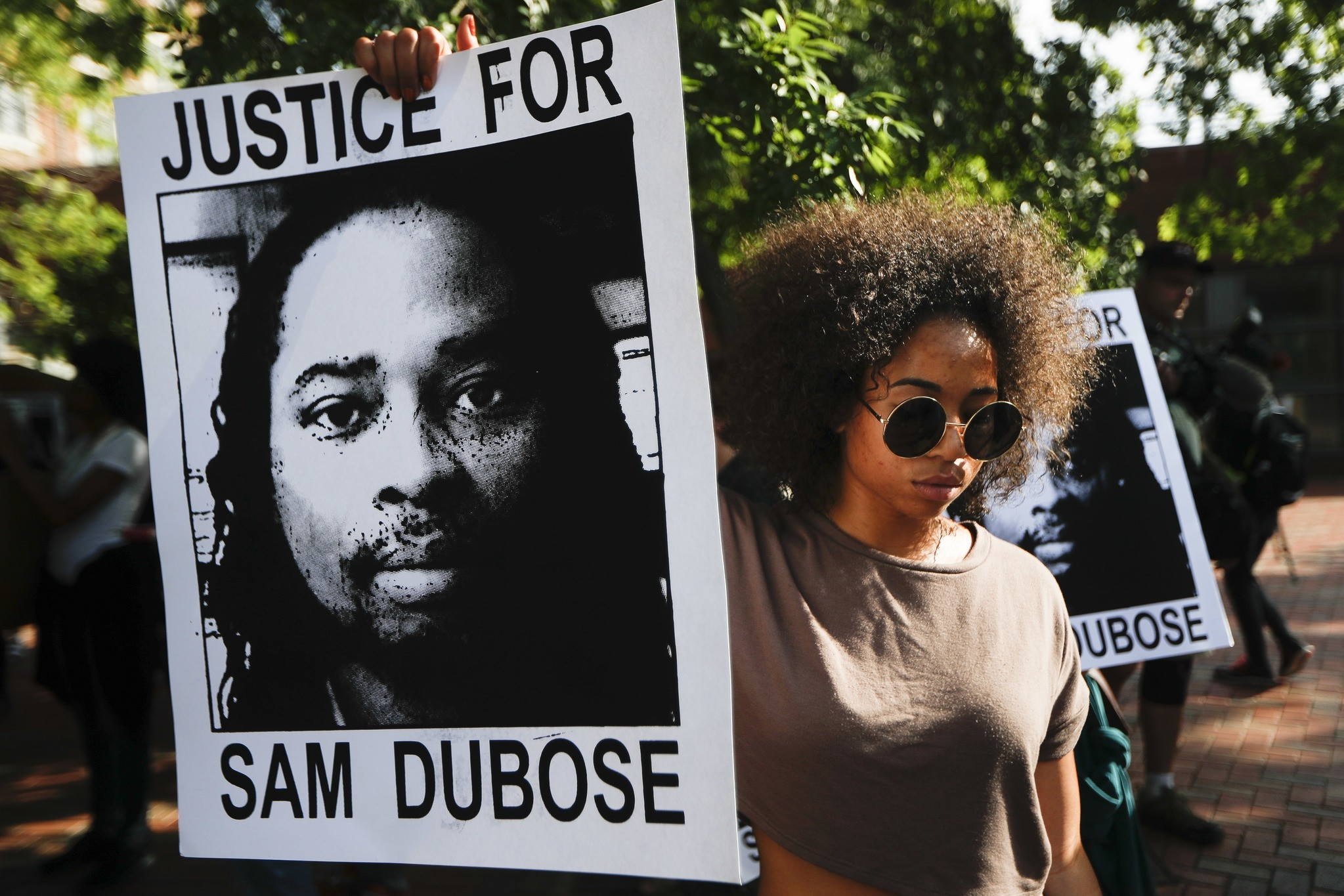 Protesters holds signs as they demand that a white former police officer be tried a third time in the fatal shooting of an unarmed black motorist, June 28, 2017. (AP Photo)