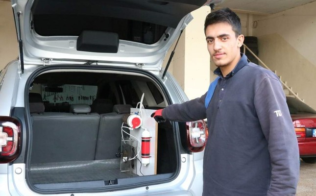 Turkish inventor Ağbaş shows the water storage unit he built for his car. (?HA)