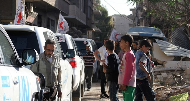 Vehicles of the International Committee of the Red Cross (ICRC), the Syrian Arab Red Crescent and the United Nations wait on a street after an aid convoy entered the rebel-held Syrian town of Daraya (AFP Photo)
