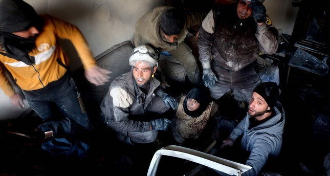 Syrian civil defence volunteers, known as the White Helmets, rescue a woman from a building following reported airstrikes on Aleppo's rebel-held district of al-Hamra on November 20, 2016. (AFP PHOTO)