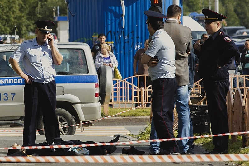 Police officers stand by the body of a man who was killed after an alleged stabbing attack, in the Siberian city of Surgut, Russia, Saturday, Aug. 19, 2017 (AP Photo)