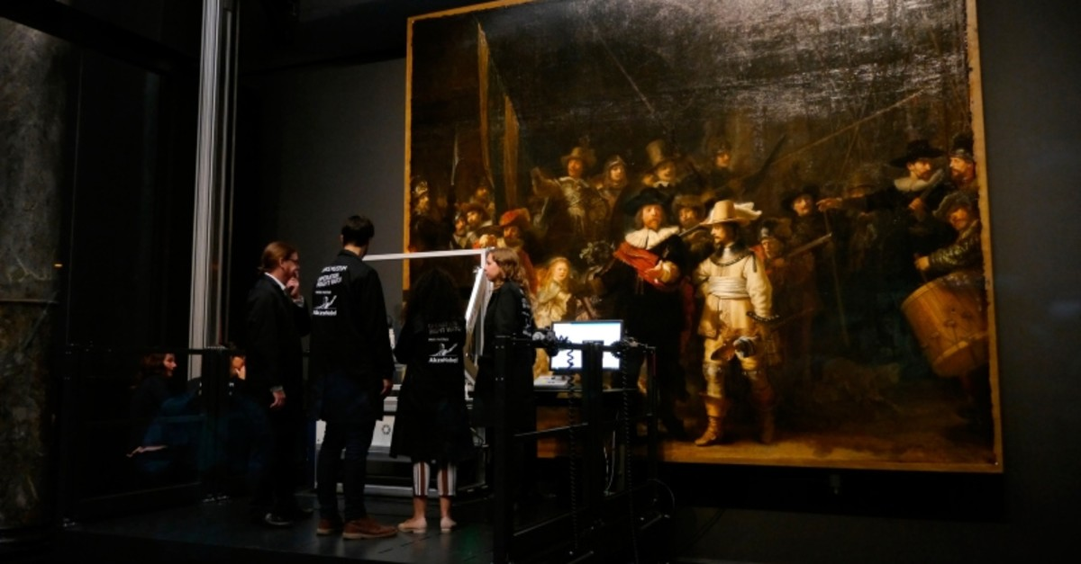 Technicians and researchers check equipment set up inside a glass chamber as they begin to study Rembrandt's 'Night Watch' masterpiece, at the Rijksmuseum in Amsterdam, Monday July 8, 2019. (AP Photo)