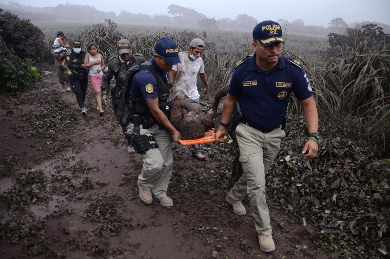 Police officers carry a wounded man after the eruption of the Fuego Volcano, in El Rodeo village, Escuintla department, 35 km south of Guatemala City on June 3, 2018 (AFP Photo)