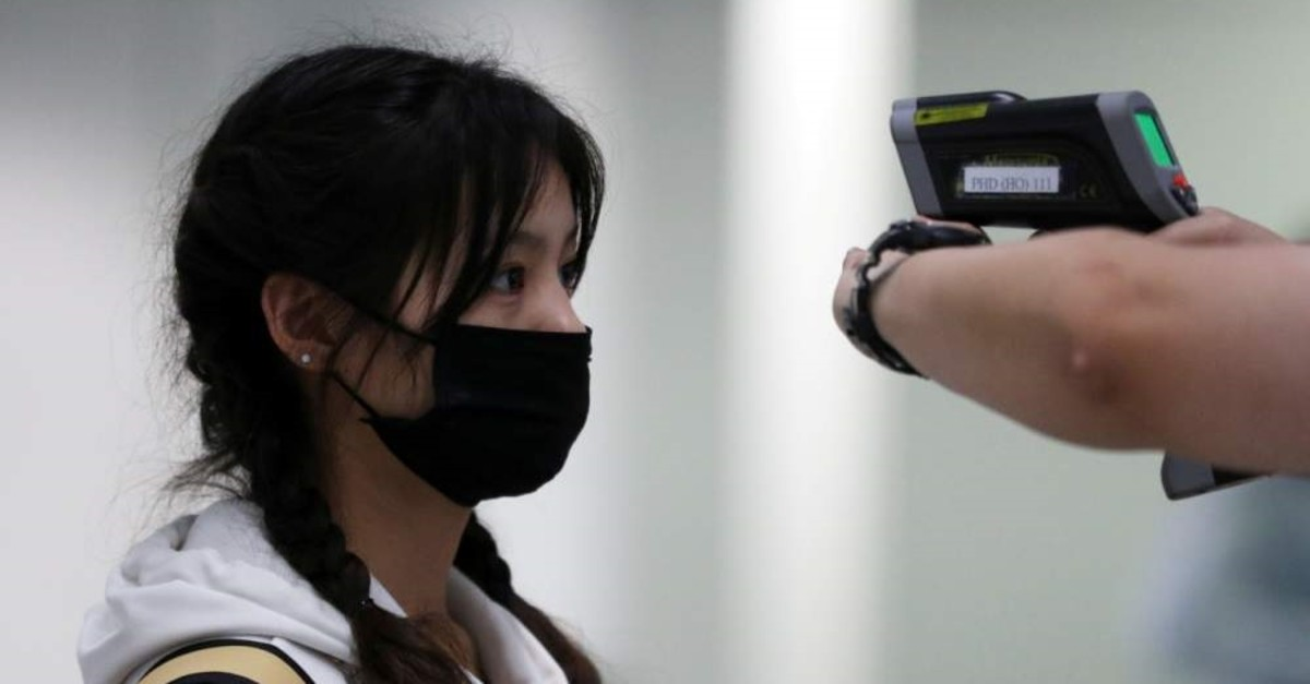 A passenger gets her temperature checked by a worker using an infrared thermometer amid coronavirus outbreak, at Hong Kong International Airport, Feb. 7, 2020. (Reuters Photo)