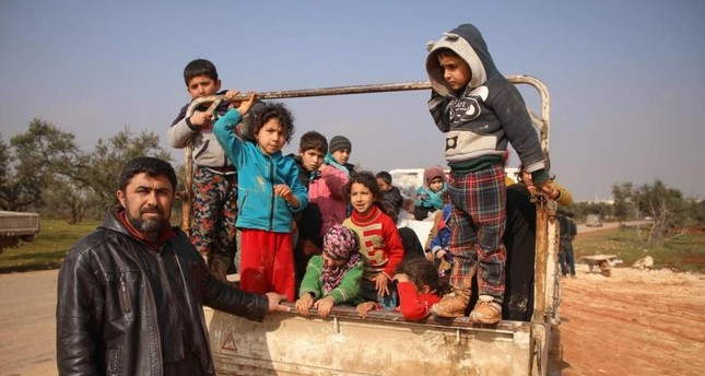 Displaced Mustafa Haj Ahmad poses for a picture with his children and relatives in a newly-established camp on the edges of Maaret Misreen town in Syria's Idlib province, Feb. 6, 2020. AFP PHOTO