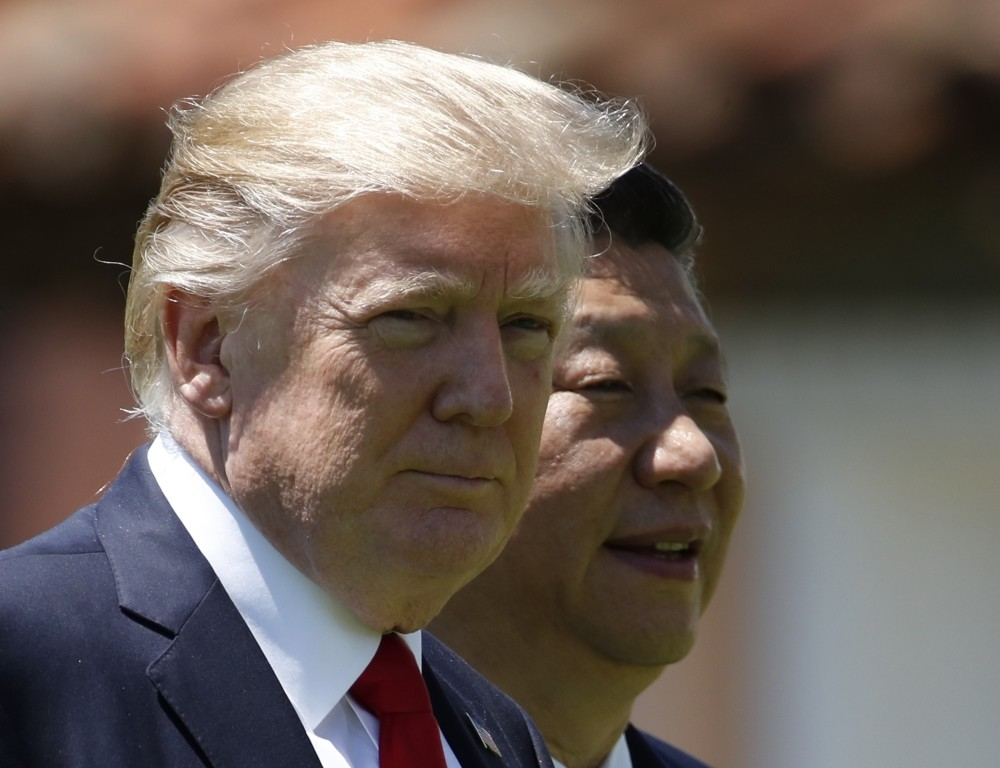 U.S. President Donald Trump, left, and Chinese President Xi Jinping walk together at Mar-a-Lago in Palm Beach, Fla.