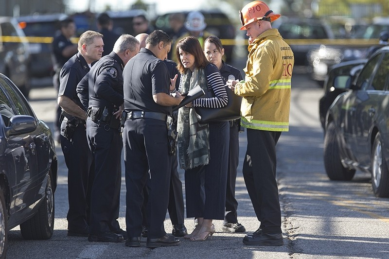 Los Angeles Fire department's Erik Scott, far right, police officers and school officials gather outside the Belmont Middle School in Los Angeles Thursday, Feb. 1, 2018 (AP Photo)