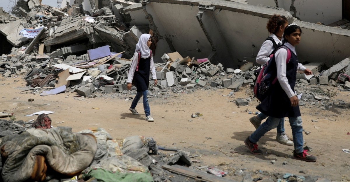 Palestinian students walk near a building that was destroyed by an Israeli airstrikes, Gaza City, May 7, 2019.