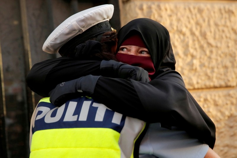 Ayah, 37, a wearer of the niqab, weeps as she is embraced by a police officer during a demonstration against the Danish face veil ban in Copenhagen, Aug 1, 2018. (Reuters Photo)